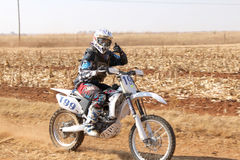 Motorbike kicking up trail of dust on sand track during rally ra Stock Images