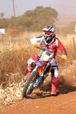 Motorbike kicking up trail of dust on sand track during rally ra Stock Photo