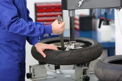 Motorbike mechanic disassembling an old tire. In a mechanical workshop Royalty Free Stock Photos