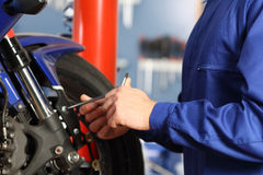 Motorbike mechanic hands disassembling parts. In a workshop with equipment in the background Royalty Free Stock Images