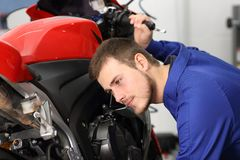 Motorbike mechanic listening engine to find failure. Motorcycle mechanic listening engine noise to find failures in a mechanical workshop Royalty Free Stock Photos