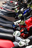 Motorbike, motorcycle scooters parked in row in city street Stock Image