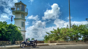Motorbike parked in front of a lighthouse Stock Images