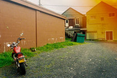 Motorbike Parked on Gravel Backroad with Film Discoloration. A motorbike is parked on a gravel alley in Alaska with orange film filter in the corner giving the royalty free stock photography