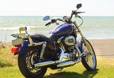 Motorbike parked on the ocean beach seaside shore line of New Zealand Stock Image