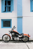 Motorbike parked on the side of a road  in front of white and blue wall Royalty Free Stock Photography