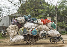 Motorbike plus cart loaded with recycled plastics. Royalty Free Stock Photography