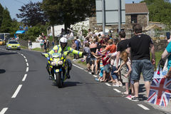 Motorbike Policeman. Olympic torch relay 26 May 2012 Bryncethin Bridgend UK Police man riding on a motorbike with hands outstretched to touch the crowds hands. A royalty free stock photo
