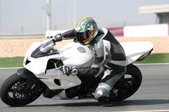 Motorbike on racetrack, leaning into sharp bend. Motorbike racing at dangerous high speed, leaning into a sharp corner on racetrack during a competition. ( stock images