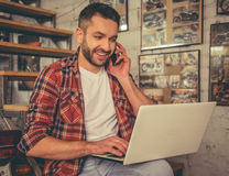 Motorbike repair shop. Handsome man in casual clothes is talking on the mobile phone, using a laptop and smiling while sitting in the motorcycle repair shop Stock Photos