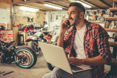 Motorbike repair shop. Handsome man in casual clothes is talking on the mobile phone, using a laptop and smiling while sitting in the motorcycle repair shop Royalty Free Stock Photography