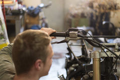 Motorbike repairing by handsome young man in his garage surround Royalty Free Stock Photography