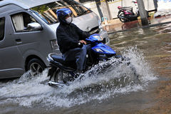 Motorbike Rider Navigates a Flooded Street. BANGKOK - NOVEMBER 1: A motorbike rider navigates a flooded street in Chinatown after the heaviest monsoon rains in Royalty Free Stock Image