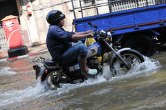 Motorbike Rider Navigates a Flooded Street Royalty Free Stock Photo