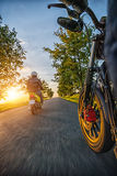 Motorbike riders driving towards beautiful sunset light on empty. Asphalt motorway. Photographed from driver perspective. Travel, freedom and transportation in Royalty Free Stock Image