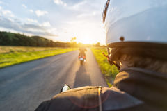 Motorbike riders driving towards beautiful sunset light on empty. Asphalt motorway. Photographed from driver perspective. Travel, freedom and transportation in Royalty Free Stock Images
