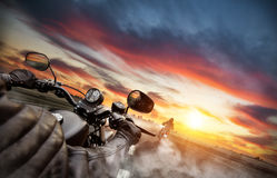 Motorbike riders driving towards cityscape panorama. On empty asphalt motorway. Photographed from driver perspective. Beautiful sunset light Stock Photography