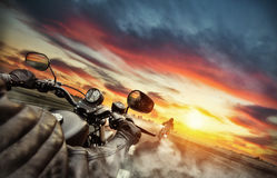 Motorbike riders driving towards cityscape panorama. On empty asphalt motorway. Photographed from driver perspective. Beautiful sunset light Royalty Free Stock Images