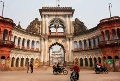 Motorbike riders move past the beautiful gates. Motorbike riders move past the beautiful historical Raj Sadan gates in Ayodhya, India. Ayodhya, with a population Stock Image