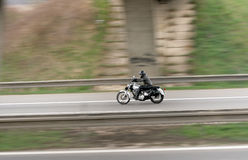 Motorbike on the road. A fast - going motorbike on highway between safety fence Stock Images