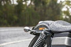 Motorbike seat in rain. A motorbike seat, rear and road in rain Stock Photography