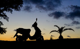 Motorbike in Silhouette. A motorbike silhouetted against a sunset sky, wth a pinapple palm next to it Royalty Free Stock Images