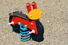 Motorbike spring toy in playground. Colorful wooden motorbike spring toy in kids playground park Stock Photo