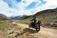 Motorbike tourism. Traveller at motorcycle in mountains. Motorbike tourism. Traveller driving motorcycle in mountains Royalty Free Stock Photos