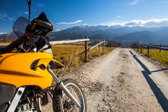 Motorbike travelling in countryside. Countryside travelling on adventure motorbike with high mountains view in background Stock Photography