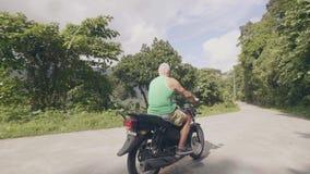 Motorbiker человека ехать на мотоцикле на дороге горы на зеленом ландшафте тропического леса Взрослый человек управляя на промежу акции видеоматериалы