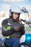 Motorbiker European woman in white open face crash helmet dialing a number in her smartphone while sitting on motorbike stock image