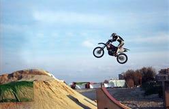 Motorbiker jump. Motor biker jumping over a sand pile. Film scan Stock Photos
