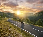 Motorbiker riding in Austrian Alps in beautiful sunset dramatic Stock Photos