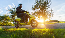 Motorbiker riding on empty road with sunset sky. Motorbiker riding on empty road with sunset light, concept of speed and touring in nature. Small motorcycle Royalty Free Stock Image