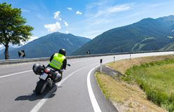 Motorbiker is riding his motorcycle bike. Motorbiker is riding his motorcycle on winding roads througt mountains in the summer sun. Rocky mountains like the alps stock photography