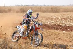 Motorbiker thumbs up kicking up trail of dust on sand track duri Stock Photo