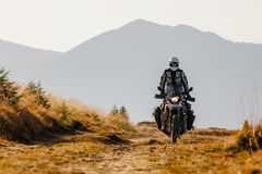 Motorbiker travelling in autumn mountains.  Royalty Free Stock Images