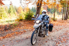 Motorbiker travelling in autumn mountains Stock Images