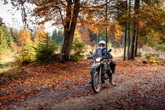 Motorbiker travelling in autumn mountains Stock Image