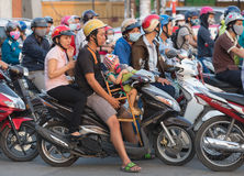 Motorbikers wait at traffic lights in Saigon city Royalty Free Stock Photo