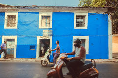 Motorbikes driving past blue walls of historical houses of indian city Royalty Free Stock Photos