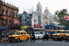 Motorbikes och bilarna som stoppas på vägen av den gammala asiatiska metropolisen Royaltyfri Bild