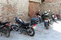 Motorbikes parked near ruins Stock Image