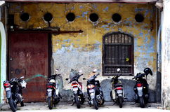 Motorbikes in Penang. A row of motorbikes are parked outside an old building on Lebuh Victoria in Penang, Malaysia Stock Images