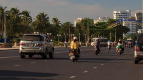 Motorbikes scooters traffic in city at dawn against palm trees stock footage