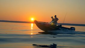 Motorboat με δύο ψαράδες επιπλέει μέσω της λίμνης ανατολής απόθεμα βίντεο