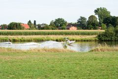 Motorboat τραβά ένα άτομο σε ένα σχοινί Wakeboarding στον ποταμό στοκ φωτογραφία με δικαίωμα ελεύθερης χρήσης
