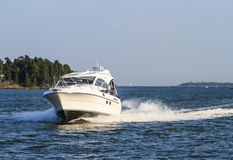 Motorboat approaching. A white motorboat approaching fast stock photo
