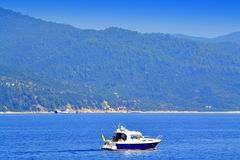 Motorboat Athos Mount. Motorboat passing by Athos Mount.September 2014,Aegean sea Greece stock photography