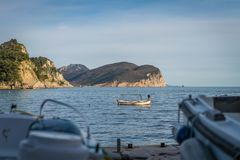 Motorboat in a bay in Petrovac. Small private boat in Petrovac bay in spring, Montenegro royalty free stock photos